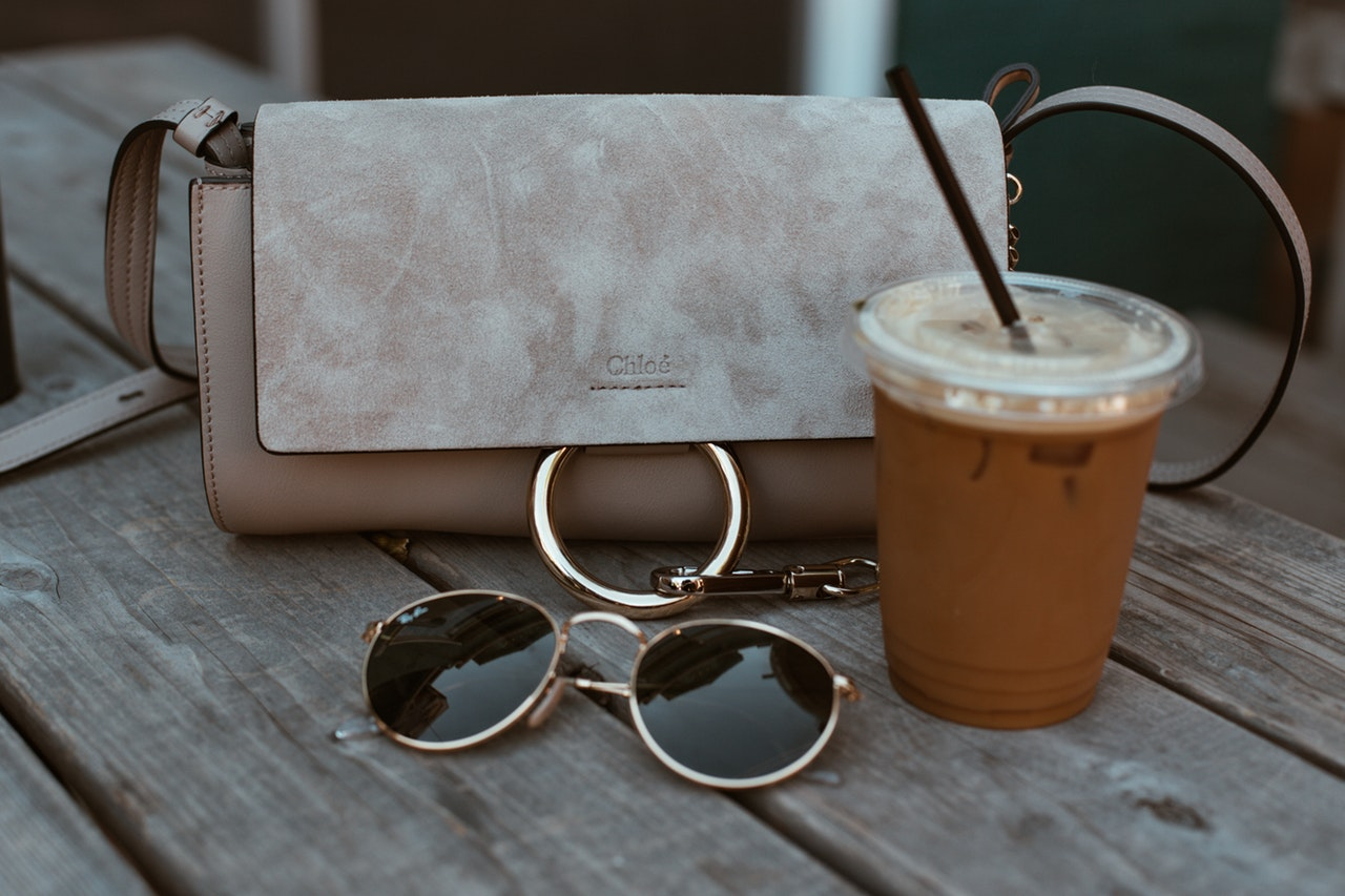 A designer handbag is sitting next to sunglasses and a coffee.