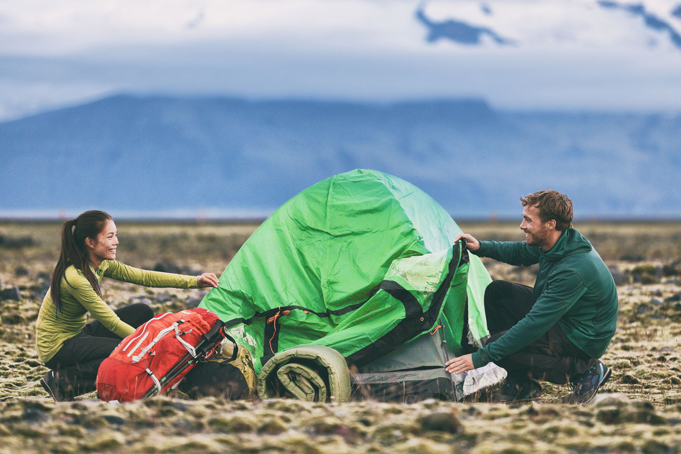Couple setting up tent in wilderness